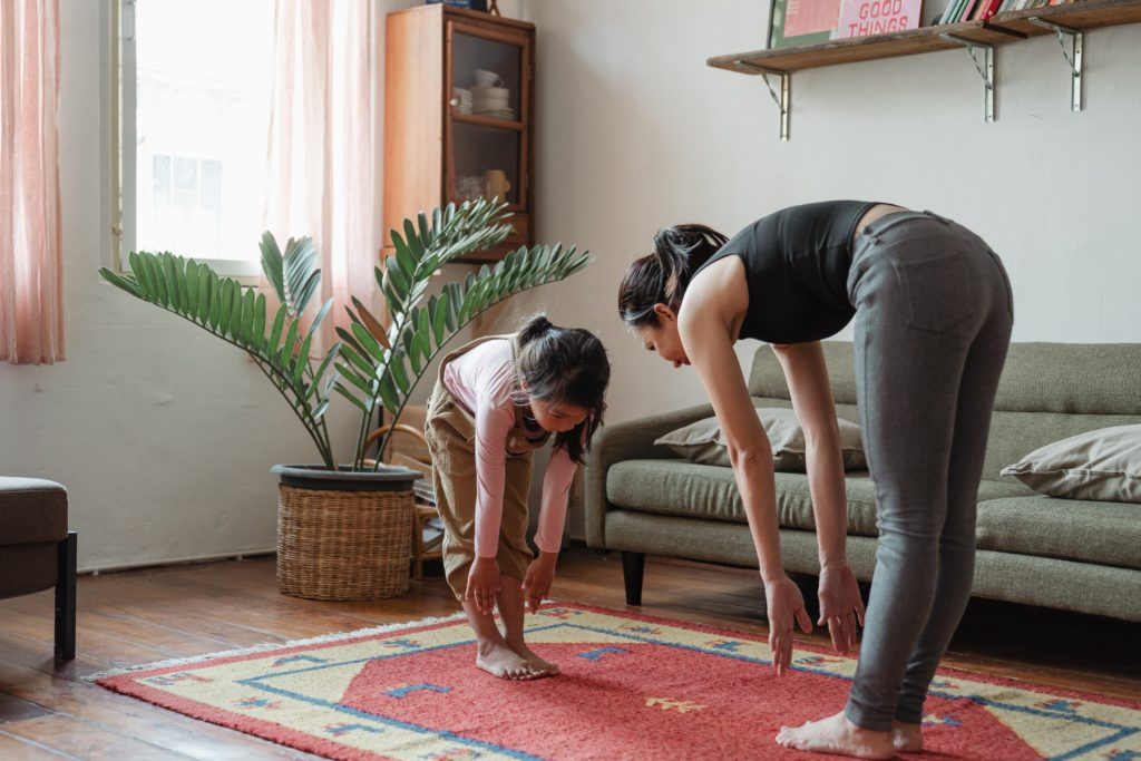 Mother and child doing yoga stretches on mat